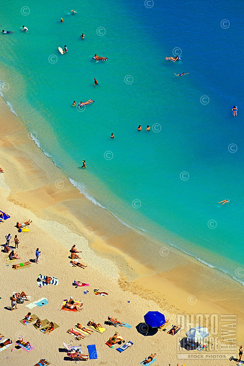 Aerial shot of happy vacationers at world famous Waikiki Beach. Photo is sliced diagonally, with upper portion showing various beautiful blue hues and the lower half shows the warm sand dotted with people relaxing.