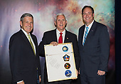 In this photo released by the National Aeronautics and Space Administration (NASA) United States Vice President Mike Pence receives a commemorative montage from Kennedy Space Center (KSC) Director, Robert Cabana, left, and Acting NASA Administrator, Robert Lightfoot, right, including stickers on the back from all of Cabana's missions, Thursday, July 6, 2017, in the green room at KSC in Cape Canaveral, Florida. Vice President Mike Pence is scheduled to speak at the event to highlight innovations made in America and tour some of the public/private partnership work that is helping to transform the center into a multi-user spaceport. <br /> Mandatory Credit: Aubrey Gemignani / NASA via CNP