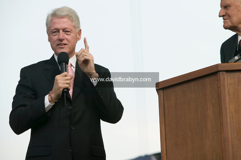 Former president Bill Clinton (L) talks on stage as evangelist Billy Graham's looks on on the second day of the preacher's three-day New York crusade at Flushing Meadows-Corona Park in Queens, NY, USA, Saturday June 25 2005.