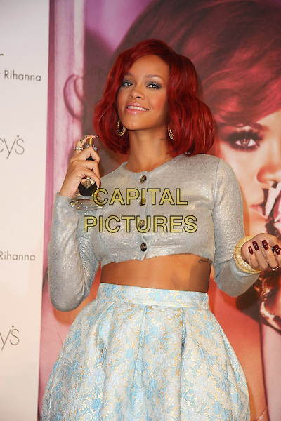 RIHANNA (Robyn Rihanna Fenty).Rihanna To Launch Her First Fragrance, Reb'l Fleur held at Macy's Lakewood Mall, Hollywood, California, USA, .18th February 2011..half length crop cropped top cardigan  grey gray  silver white skirt midriff holding bottle perfume bracelets spraying smiling .CAP/ADM/TB.©Tommaso Boddi/AdMedia/Capital Pictures.