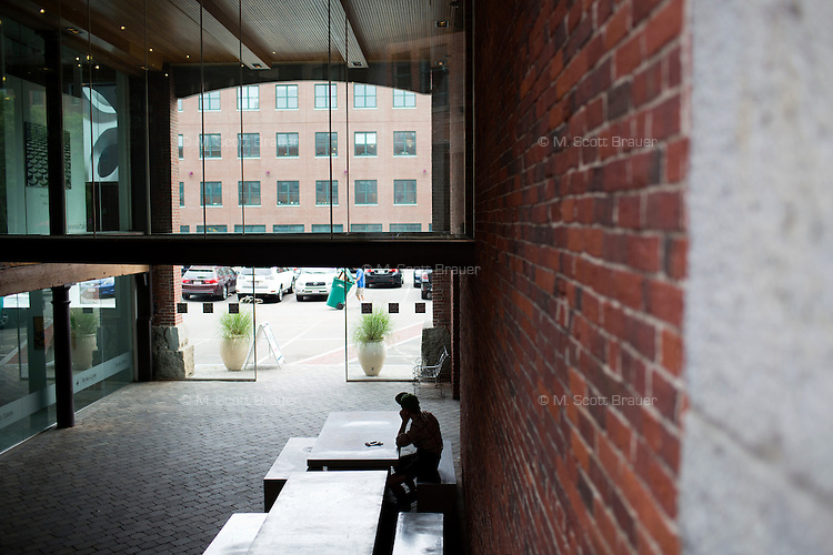 A man sits at a cafe table near boutiques on Thayer Street in the South End of Boston, Massachusetts, USA.