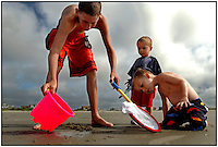 Two young boys, brothers, play with one another and a family friend during a family vacation to the beach near Charleston, SC.  Model released image may be used to illustrate other destinations or concepts.