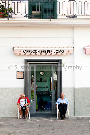 Two Italian men wait outside the local barber, in the small village of Minori on the Amalfi Coast, Italy
