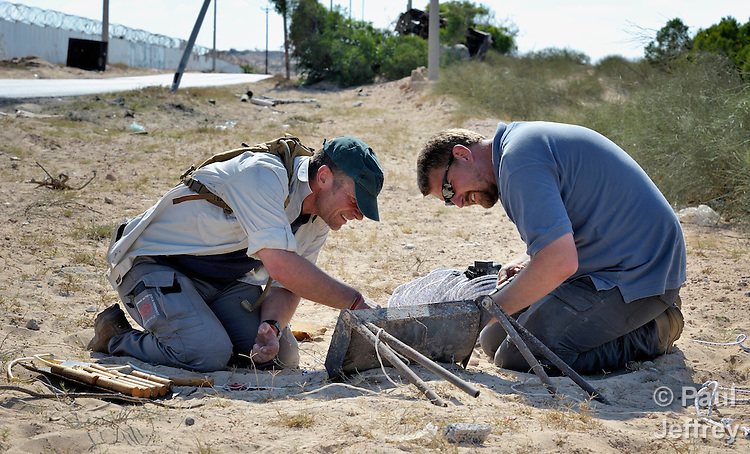 Fred Pavey (left) and Johnny Thomsen, explosive ordnance disposal technicians, neutralize an improvised explosive device alongside a heavily traveled road in Misrata, the besieged Libyan city where civilians and rebel forces are surrounded on three sides by forces loyal to Libyan leader Moammar Gadhafi, on June 15. Thomsen, from Denmark, and Pavey, from the United Kingdom, are part of a team from the ACT Alliance which arrived in Misrata on June 13. They work with the humanitarian mine action program of DanChurchAid, which is a member of the ACT Alliance. The device used a Claymore-type mine connected to both victim- and command-activated switches. Photo by Paul Jeffrey/ACT Alliance.