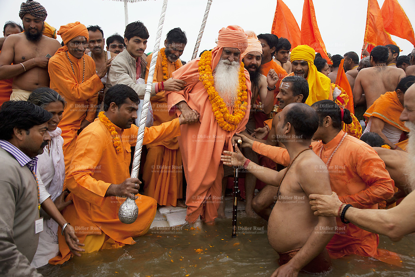 "India. Uttar Pradesh state. Allahabad. Maha Kumbh Mela. Royal bath on Basant Panchami Snan (fifth day of the new moon). The ritual ""Royal Bath"" is timed to match an auspicious planetary alignment, when believers say spiritual energy flows to earth. A Guru wearing saffron clothes and a turban will take a dip in Sangam with his disciples and worships the river Ganges. The Kumbh Mela, believed to be the largest religious gathering is held every 12 years on the banks of the 'Sangam'- the confluence of the holy rivers Ganga, Yamuna and the mythical Saraswati. In 2013, it is estimated that nearly 80 million devotees took a bath in the water of the holy river Ganges. The belief is that bathing and taking a holy dip will wash and free one from all the past sins, get salvation and paves the way for Moksha (meaning liberation from the cycle of Life, Death and Rebirth). Bathing in the holy waters of Ganga is believed to be most auspicious at the time of Kumbh Mela, because the water is charged with positive healing effects and enhanced with electromagnetic radiations of the Sun, Moon and Jupiter. The Maha (great) Kumbh Mela, which comes after 12 Purna Kumbh Mela, or 144 years, is always held at Allahabad. Uttar Pradesh (abbreviated U.P.) is a state located in northern India. 15.02.13 © 2013 Didier Ruef"