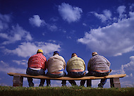 Four construction workers expose their rear ends while leaning over on a bench to eat lunch