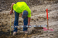 A worker checks the depth of excavation where a new parking lot for the library is being built.