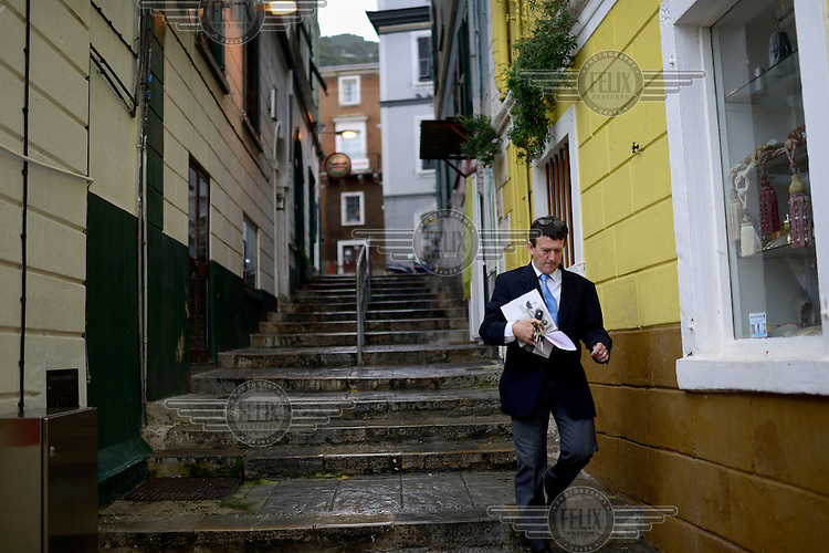 A man jogs down a flight of stairs in an old part of the town.
