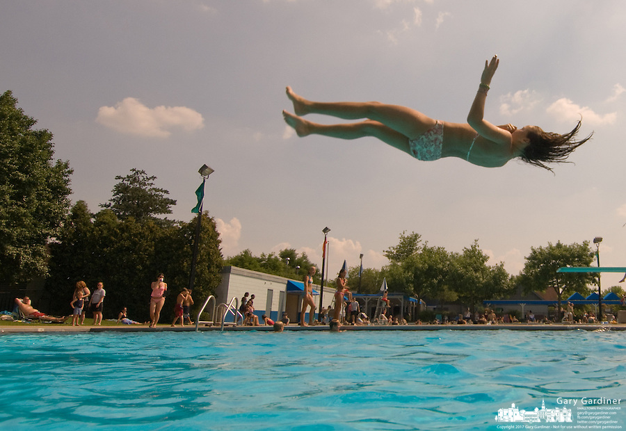 Young girls lies horizontal as she makes a dive at a municipal pool.