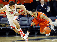 Virginia guard Joe Harris (12) goes after a loose ball with Clemson forward/center Devin Booker (31) during the game against Clemson Thursday in Charlottesville, VA.