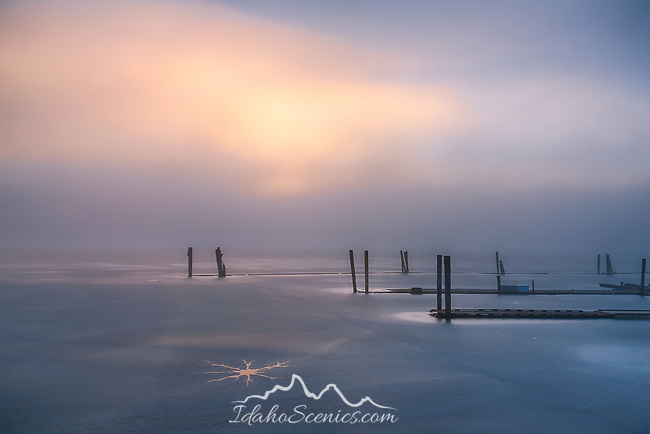 Idaho, North, Benewah County, PLummer, Heyburn State Park.The sun glows through morning fog over an ice covered Lake Chatcolet in winter.
