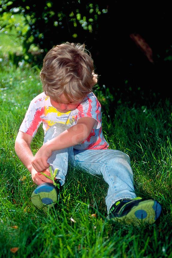 Boy tying his shoe.