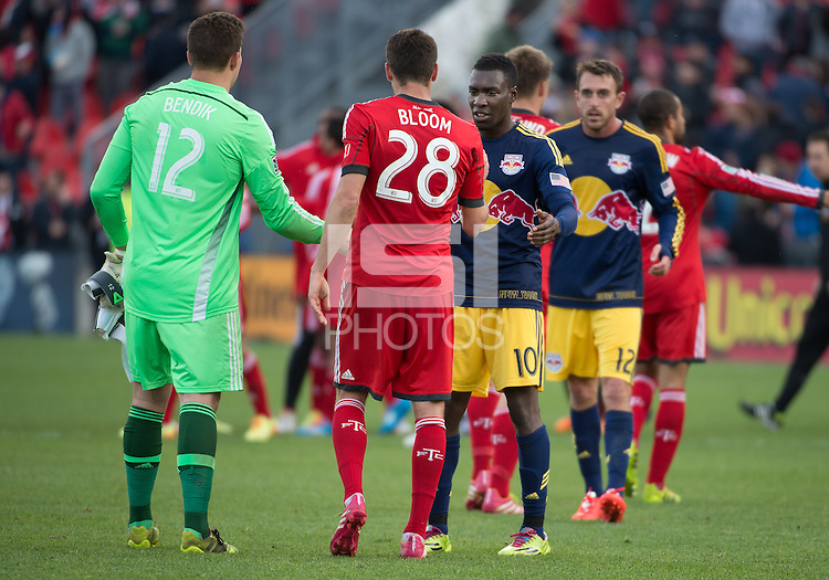 Toronto, Ontario - May 17, 2014: New York Red Bulls midfielder Lloyd Sam #10 shakes hands with Toronto FC defender Mark Bloom #28 and Toronto FC goalkeeper Joe Bendik #12 in a game between the New York Red Bulls and Toronto FC at BMO Field. Toronto FC won 2-0.