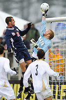 Akron Zips goalkeeper David Meves (24) pushes the ball over the goal as Virginia Cavaliers Jordan Evans (2) attempts a header. The Virginia Cavaliers defeated the Akron Zips 3-2 in a penalty kick shoot out after a scoreless game and overtime in the finals of the 2009 NCAA Men's College Cup at WakeMed Soccer Park in Cary, NC on December 13, 2009.