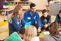 Salve Regina volunteers Abigail Verille,'18, and Christopher Nova,'17, work with children on language skills at the Pell School in Newport as part of a Modern Languages Program.