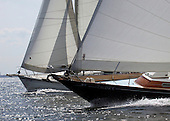 The black sloop is a powerful sailing yacht. It is sailing faster and overtaking the white hulled yacht.  The owner can be very proud of his yacht.