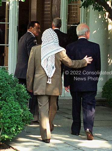 "Palestinian leader Yasser Arafat puts his hand on the back of Israeli Prime Minister Yitzhak Rabin as they walk to the East Room of the White House in Washington, D.C. on September 28, 1995.  The two leaders were at the White House to sign the ""Oslo 2"" accords between the Palestine Liberation Organization (PLO) and Israel..Credit: Arnie Sachs / CNP"