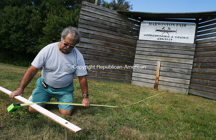HARWINTON,  CT 24 September 2005 -092405BZ02- Jack Compresi, superintendent of woodchopping and sawing for the Harwinton Fair, measures the distance from the backstop for proper placement of a foul line to be used in the ax throw competition at the fair next week.   <br /> Jamison C. Bazinet / Republican-American
