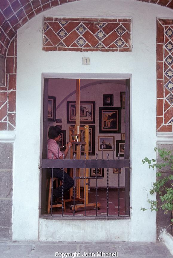 Artist painting a picture in his studio, Barrio del Artista, city of Puebla, Mexico