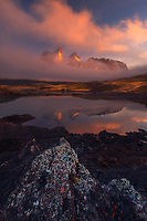 Los Cuernos del Paine peeks through low clouds illuminated by the rising sun on a foggy morning.<br />