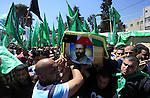 Palestinian mourners wave the green flag of the Islamist movement Hamas as they attend the funeral of two Hamas members, Adel and Imad Awadallah, killed in 1998, after Israel returned the remains of four Palestinians to their families to their families, on April 30, 2014 in the West Bank city of Ramallah. Photo by Issam Rimawi