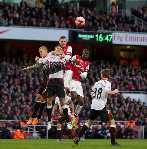 16.02.2014 London, England.  Per Mertesacker of Arsenal (middle) jumps with Daniel Agger and Martin Škrteľ of Liverpool during the FA Cup 5th Round game between Arsenal and Liverpool from the Emirates Stadium.