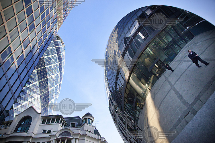Part of the Swiss Re Tower (the Gherkin) and reflections of office buildings in the City of London.