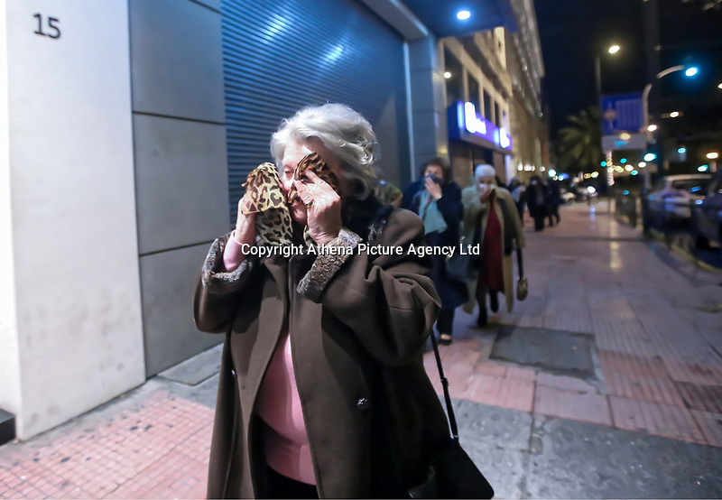 Pictured: A woman attempts to protect herself from the effects of teargas used by riot police against protesters in central Athens, Greece.<br /> Re: Official visit of German Chancellor Angela Merkel  to Athens, Greece.