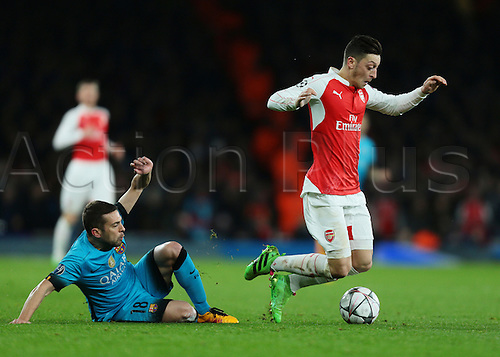 23.02.2016. Emirates Stadium, London, England. UEFA Champions League. Arsenal versus Barcelona. Arsenal Midfielder Mesut Özil is fouled by Barcelona Defender Jordi Alba
