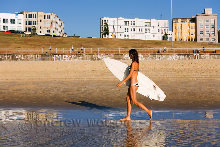 A young surfer walks along the sands of Bondi at Sydney's eastern beaches.  Bondi Beach, Sydney, New South Wales, AUSTRALIA.  © Andrew Watson / Axiom
