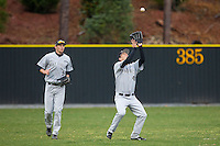 Grant Shambley (43) of the Wake Forest Demon Deacons settles under a fly ball as Evan Stephens (5) looks on during the game against the Davidson Wildcats at Wilson Field on March 19, 2014 in Davidson, North Carolina.  The Wildcats defeated the Demon Deacons 7-6.  (Brian Westerholt/Four Seam Images)