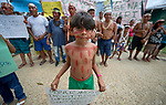 Indigenous people, including a young Indian boy, march through the streets of Atalaia do Norte in Brazil's Amazon region on March 27, 2019, protesting a central government plan to turn control of health care over to municipalities, in effect destroying a federal program of indigenous health care. Indian rights activists are worried that the government of President Jair Bolsonaro is reducing or eliminating protections for the country's indigenous people.