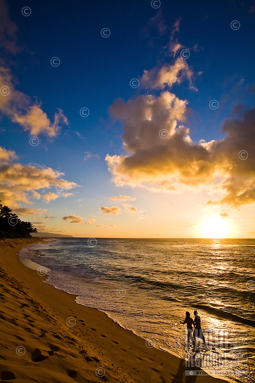 Couple walking down world famous Sunset Beach