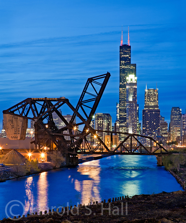 The Chicago River reflects the blue of the sky in the early evening twilight.