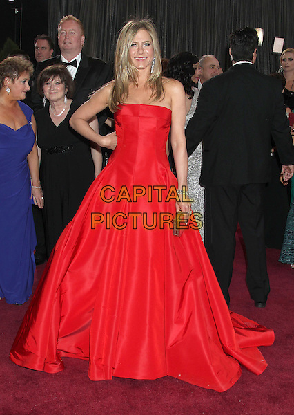 Jennifer Aniston (wearing Valentino).85th Annual Academy Awards held at the Dolby Theatre at Hollywood & Highland Center, Hollywood, California, USA..February 24th, 2013.oscars full length red strapless dress gown gold clutch bag hand on hip.CAP/ADM/RE.©Russ Elliot/AdMedia/Capital Pictures.