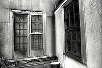 Screen doors & windows of abandoned building<br />