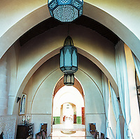 A trio of Moroccan carved brass lanterns hangs from the vaulted ceiling in the dining room