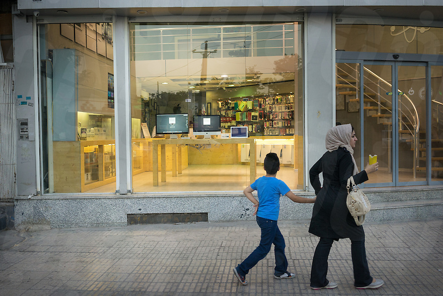 June 25, 2014 - Shiraz, Iran. A mother and her son walk in front of a recently opened unofficial Apple reseller. © Thomas Cristofoletti / Ruom