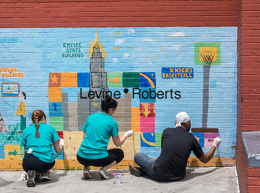 Volunteers touch-up a mural on the side of PS 33 the Chelsea School in the Chelsea neighborhood of New York on Saturday, June 6, 2015. (© Richard B. Levine)