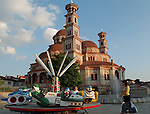 Korca/Korce-Albania - August 02, 2004---Orthodox church and a merry-go-round (carousel) for children in the city of Korca; region/village of project implementation by GTZ-Wiram-Albania (German Technical Cooperation, Deutsche Gesellschaft fuer Technische Zusammenarbeit (GTZ) GmbH); religion-culture---Photo: Horst Wagner/eup-images