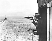 Doctor Robert H. Goddard observes the launch site from his launch control shack while standing by the firing control panel. From here he can fire, release, or stop testing if firing was unsatisfactory. Firing, releasing, and stop keys are shown on panel. The rocket is situated in the launch tower. .Credit: NASA via CNP