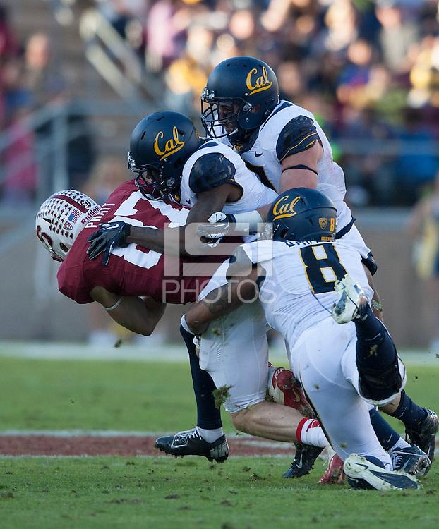 California defenders' Kameron Jackson, Michael Barton and Lucas King tackle Jordan Pratt of Stanford during the game at Stanford Stadium in Palo Alto, California on November 23rd, 2013.  Stanford defeated California, 63-13.