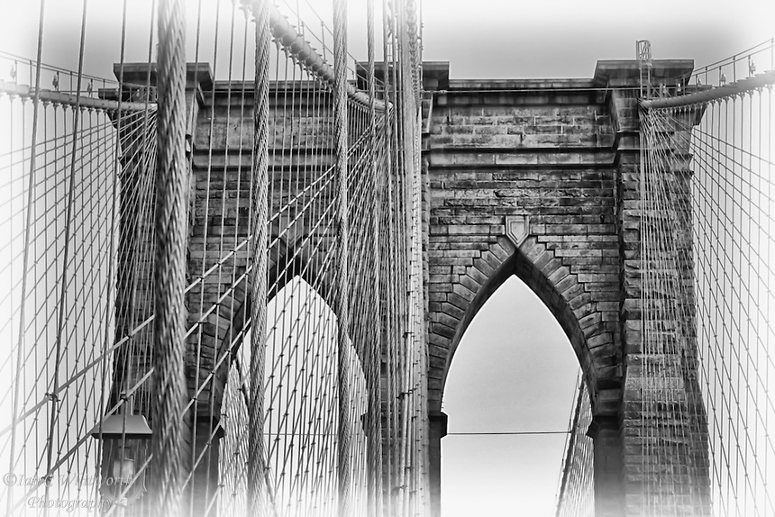 A black and white view of a portion of the landmark Brooklyn Bridge in New York City.