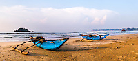 Panoramic photo of traditional fishing boats on Weligama Beach, South Coast of Sri Lanka, Asia. This is a panoramic photo of traditional fishing boats on Weligama Beach on the South Coast of Sri Lanka, Asia. Weligama Beach has a thriving fishing community, resulting in hundreds of these traditional Sri Lankan fishing boats littering the sandy beach.