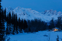 Winter landscape of house / cabin with lights on at dawn with Chugach Mountains in background.  Southcentral, Alaska in Glacier View area.    February 2016