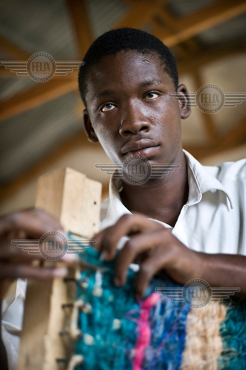 Sikudheni, who is blind, receives vocational training from Father Mashauri at his school for children and young people with disabilities. The school is supported by NGO Terre Des Hommes..