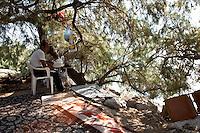 Grecia, Patrasso 2011: rifugiati afgani  accampati nei boschi lungo la spiaggia. Un uomo seduto sotto a un albero. Per terra coperte e tappeti. Grece ville de Patras  2011 - refugies  afghans organisent leur vie au bord de la plage