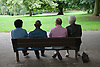 Group of older people sitting on a bench in the park,