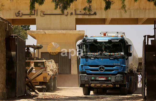 A member of Egyprian security forces stands guard as trucks carrying fuel enter the southern Gaza Strip from Egypt through the Rafah border crossing on June 21, 2017. Egypt began to deliver a million litres of fuel to Gaza, a Palestinian official said, in an attempt to ease the Palestinian enclave's desperate electricity crisis. The fuel, trucked in through the Rafah border between Egypt and Gaza, will be routed to the territory's only power station -- closed since April due to fuel shortages. Photo by Ashraf Amra