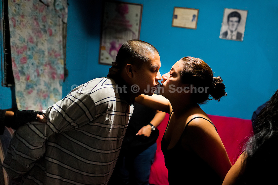 An alleged Barrio 18 gang member gives a goodbye kiss to his wife after being detained by the special anti-gang unit (Unidad Antipandillas) during a night raid in Soyapango, a gang neighborhood in San Salvador, El Salvador, 13 December 2013. Although the murder rate in the country has dropped significantly, after a truce between two major street gangs (Mara Salvatrucha and Barrio 18) was agreed in 2012, the lack of security and violence are still the main issues in people's daily life. Due to the fact the gangs have never stopped their criminal activities (extortions, distribution of drugs and kidnappings), the Police anti-gang forces keep running their operations and chasing the 'homeboys' (how the gang's foot soldiers usually call themselves) in the poor, socially deprived suburbs of Salvadoran cities.